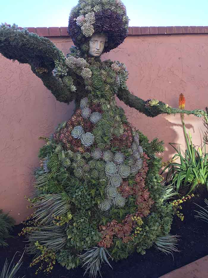 standing lady topiary form with plants aded
